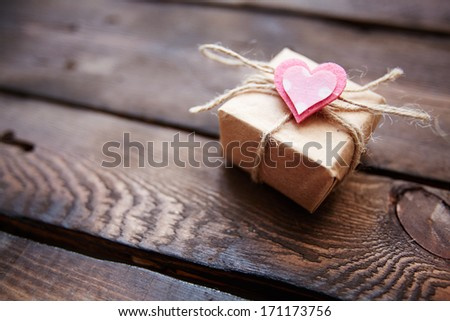 Image of valentine giftbox with small pink heart on wooden background - stock photo