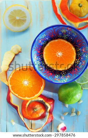Image of various citrus fruits: lime, orange, lemon, tangerine on used blue cutting board with ornated plate - stock photo