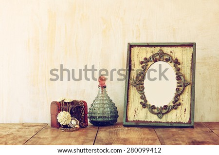 image of victorian vintage antique classical frame, jewelry and perfume bottles on wooden table. filtered image  - stock photo