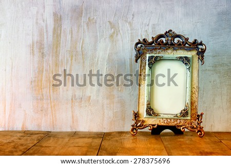 Image of victorian vintage antique classical frame on wooden table. retro filtered image - stock photo