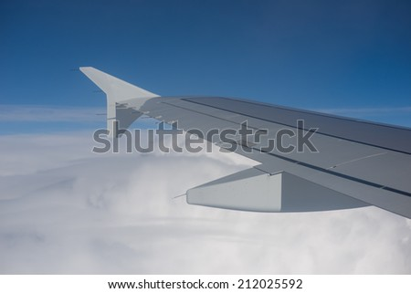 Image of View from airplane window with blue sky and white clouds