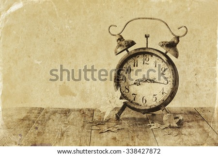 image of vintage alarm clock next to autumn leaves on wooden table in front of wooden background. old style photo  - stock photo