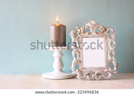 image of vintage antique classical frame and burning candle on wooden table - stock photo