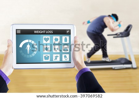 Image of weight loss applications on the digital tablet screen with overweight person doing workout on treadmill