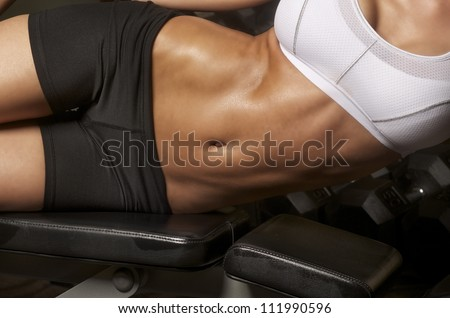Image of well toned athletic young woman with tight defined abs in stomach - stock photo