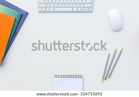 Image of White Office Desk with Computer Keyboard Mouse Color Pencils Booklets Glasses and other Supplies Top View - stock photo