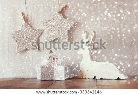 image of white wooden reindeer and glitter stars hanging on rope over glitter silver background. retro filtered with glitter overlay  - stock photo