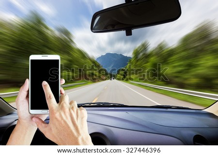 Image of windshield on the road ,way and highway, Drivers use smart phones while driving . - stock photo