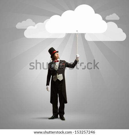 Image of wizard in hat catching clouds - stock photo