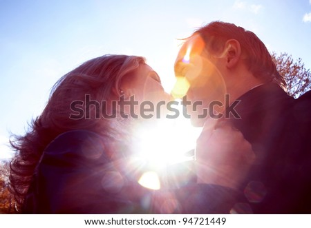Image of woman and man kissing each other outside - stock photo