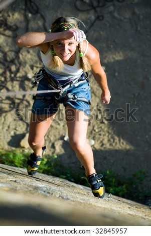 Image of woman hanging on the rope and looking at camera - stock photo