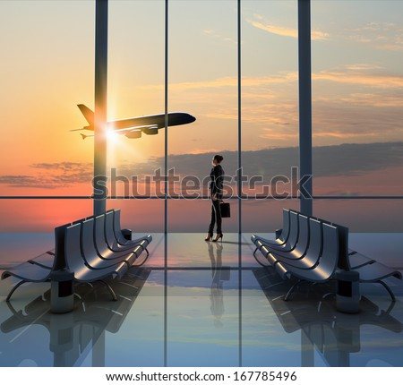 Image of woman in airport looking at taking off airplane - stock photo