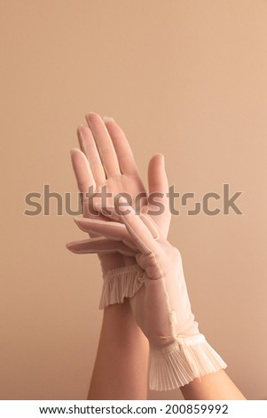 Image of woman's forearms and hands modeling vintage sheer see through gloves.