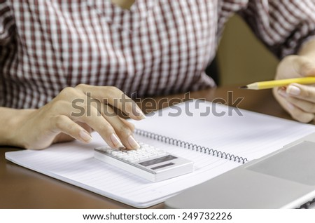 Image of woman using a calculator while working