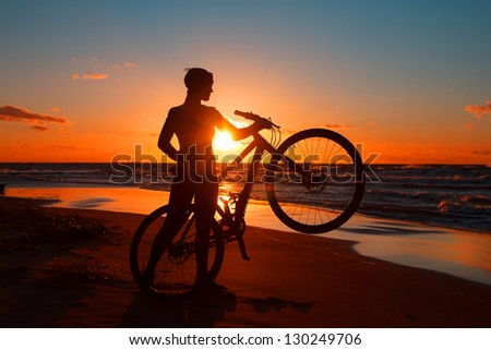 Image of woman with a bicycle on the sea - stock photo