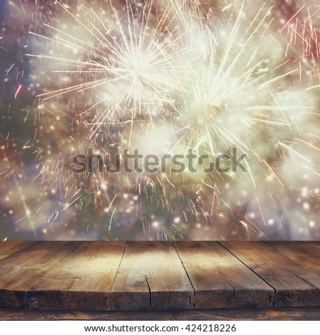 image of wooden table in front of blurred fireworks background  - stock photo