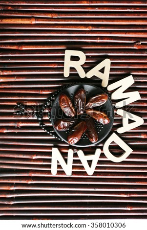Image of word RAMADAN with rosary and dates fruit on wooden background, close up - stock photo