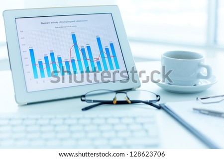 Image of workplace with electronic document, cup and eyeglasses on it - stock photo