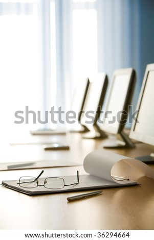Image of workplace with paper, eyeglasses, pen and monitors near by - stock photo