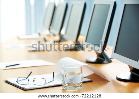 Image of workplace with paper, glass of water, eyeglasses and monitors near by - stock photo