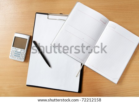 Image of workplace with paper, notepad, pen and palmtop gadget on it - stock photo