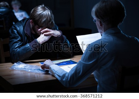 Image of worried male suspect during police hearing - stock photo