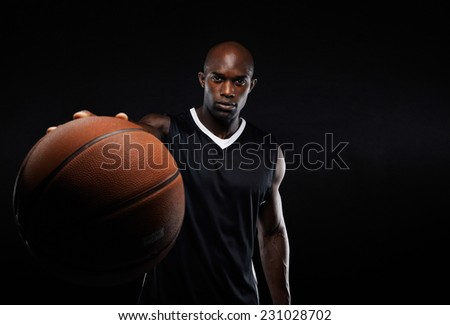 Image of young african american man in sports jersey holding a basketball. Professional basketball player against black background. - stock photo