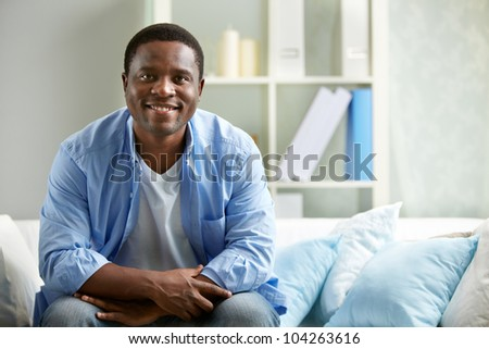 Image of young African man sitting on sofa and looking at camera - stock photo