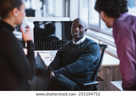 Image of young afro american man sitting at desk in office. Young executives at work. - stock photo