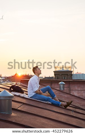 image of young attractive man relaxing on the roof - stock photo
