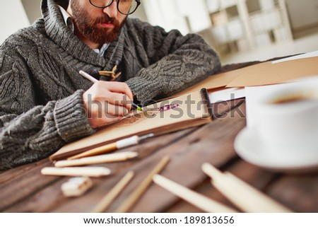 Image of young bearded man drawing - stock photo
