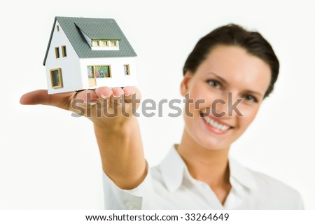 Image of young beautiful woman presenting model of house
