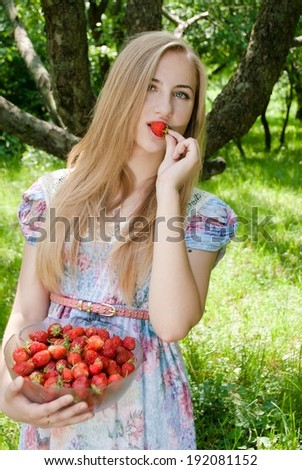 image of young blond pretty woman happy teen girl eating strawberry from huge bowl on summer day green garden outdoors background - stock photo