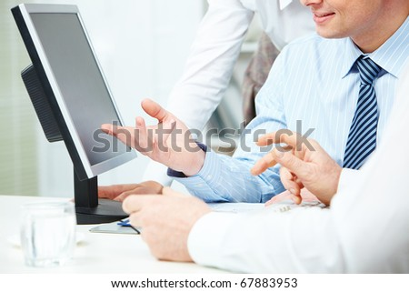 Image of young businessman hand pointing at computer monitor while making presentation