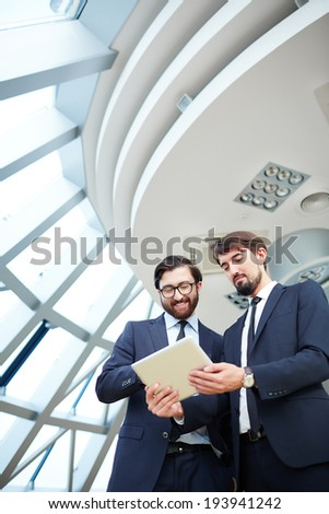 Image of young businessman holding touchpad while listening to explanation of his colleague at meeting - stock photo