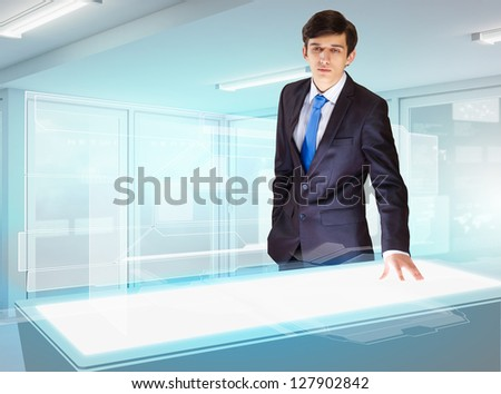 Image of young businessman looking at high-tech picture - stock photo