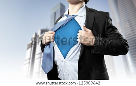 Image of young businessman showing superhero suit underneath his shirt standing against city background - stock photo
