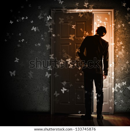 Image of young businessman standing with back opening door - stock photo