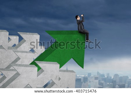 Image of young businessman using binoculars to look at the sky while sitting on the green upward arrow - stock photo