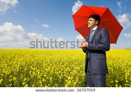 Image of young businessman with red umbrella in flower field