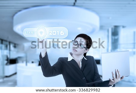 Image of young businesswoman holding notebook computer and pressing start button on the virtual screen - stock photo