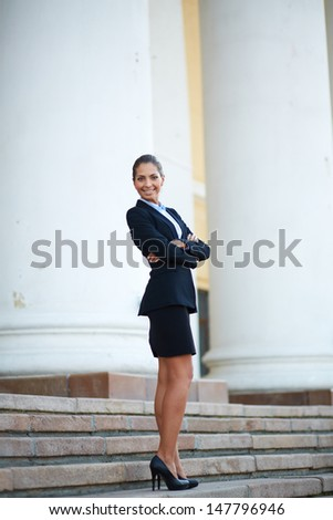 Image of young businesswoman in suit standing on steps of building - stock photo