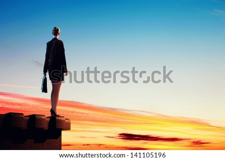 Image of young businesswoman standing on top of building - stock photo