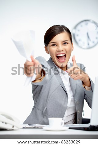 Image of young businesswoman with crumbled paper showing thumbs up - stock photo