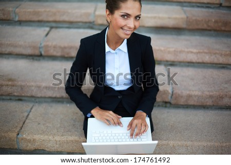 Image of young businesswoman with laptop looking at camera while networking on steps of building - stock photo