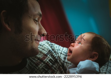 Image of young dad with cute little daughter in his arms. Father and newborn baby child indoor. - stock photo