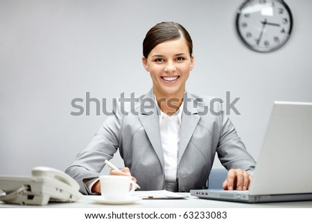 Image of young employer looking at camera while planning work in office - stock photo