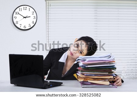 Image of young female businesswoman looks tired, working overtime with laptop and paperworks - stock photo