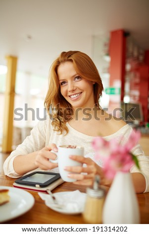 Image of young female having cup of coffee in cafe