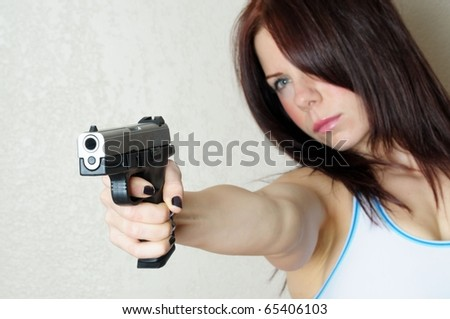 Image of young female poing gun at someone breaking and entering - stock photo